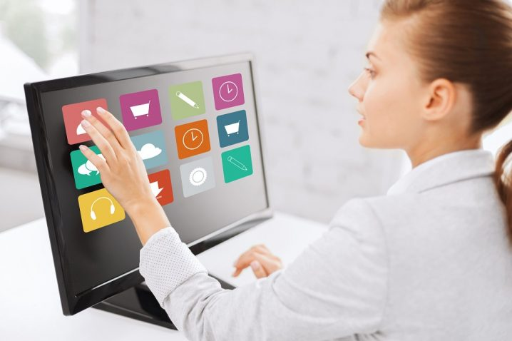 business, people, technology and media concept - woman with application icons on computer touchscreen in office