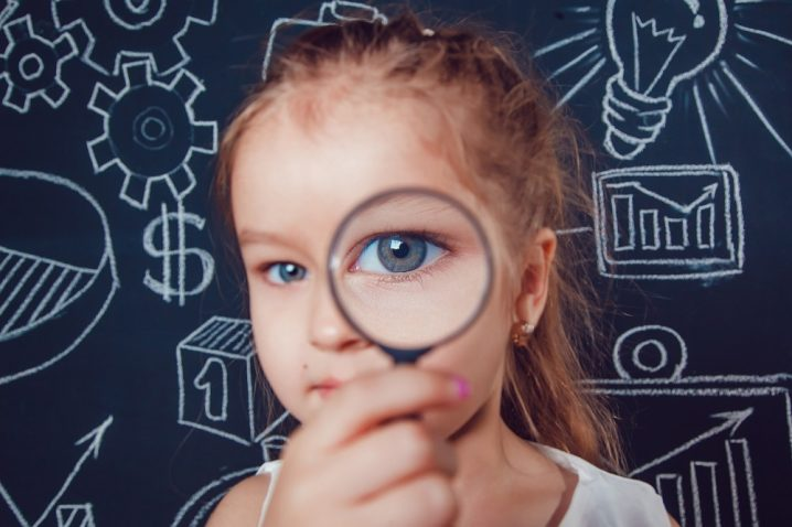 Little girl looking through a magnifying glass on dark background with pattern