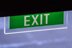 Green Illuminated Corporate Office Exit Sign Closeup.