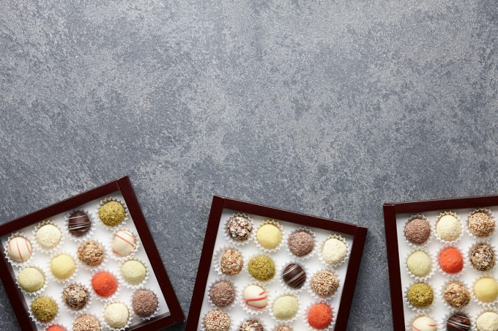 Various chocolate truffle candies in a box on gray stone background