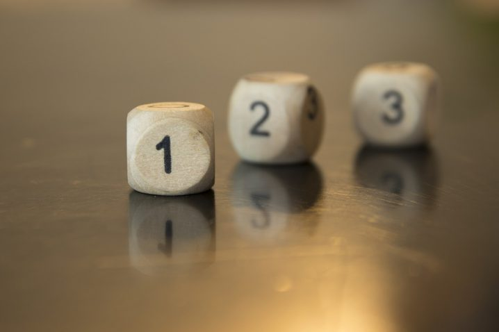 Rolling three dice on a wooden desk. Rolling the dice concept for business risk, chance, good luck or gambling.