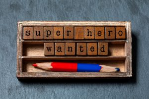 Super hero wanted phrase. Recruiting and personal searching concept quote. Vintage box, wooden cubes with old style letters, red blue pencil. Gray textured background. Close-up, up view, soft focus.
